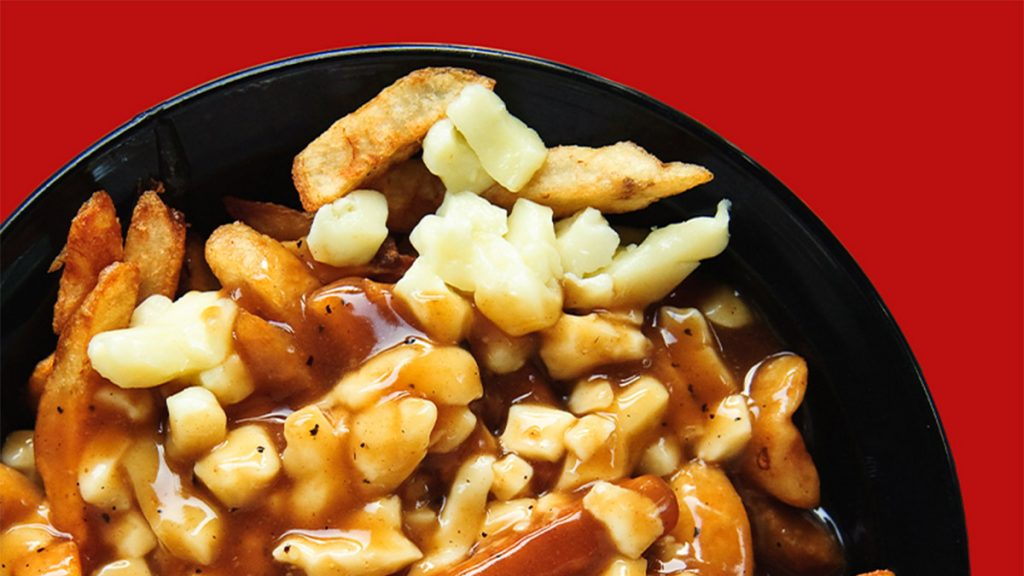 bowl of poutine on red background