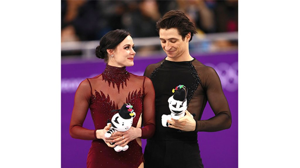 tessa and scott holding stuffed animals at the olympics