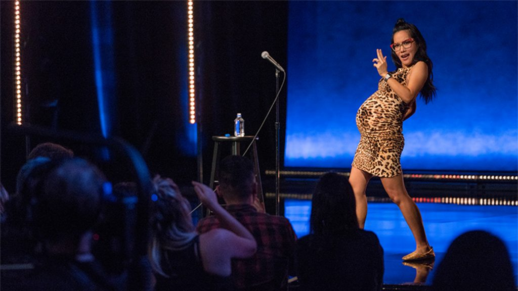 ali wong on stage in a leopard dress making a gun with her hand