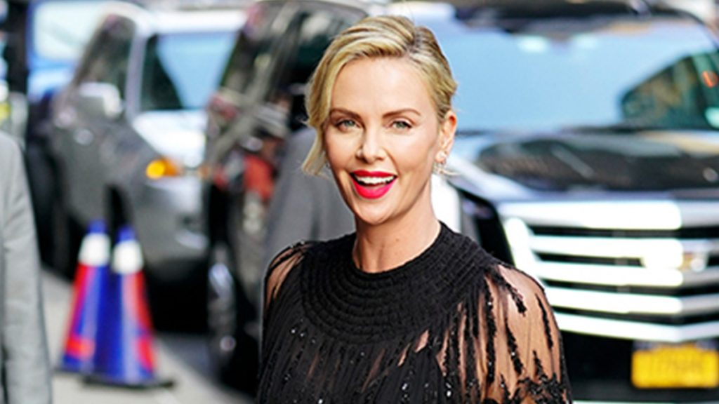 charlize theron in a black dress smiling