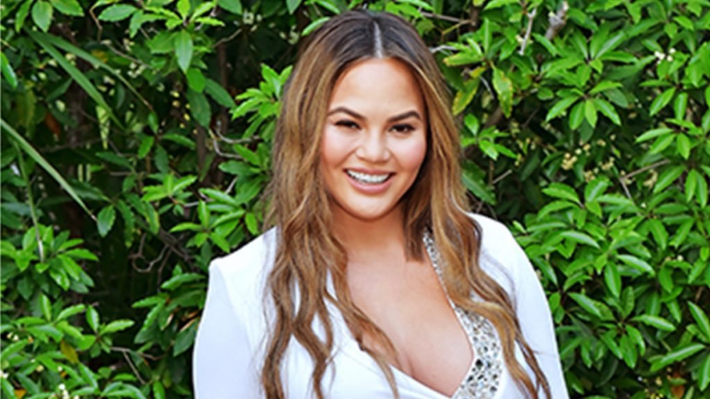 chrissy teigen smiles in white dress standing in front of wall of leaves