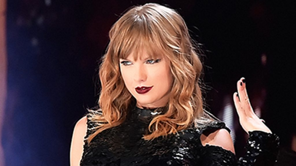 taylor swift on stage with dark red lips