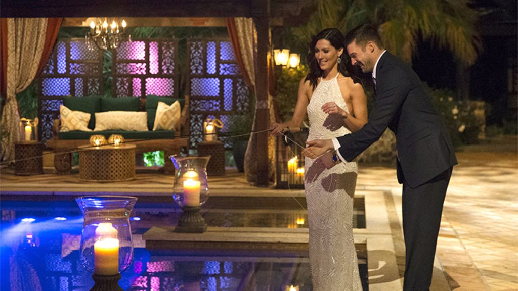 the bachelorette becca in a white gown next to the pool with contestant garrett